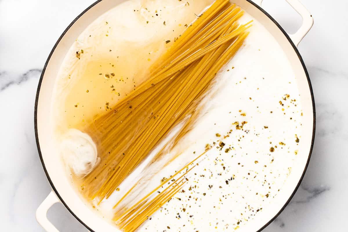 Large white pan filled with ingredients to make garlic Parmesan pasta