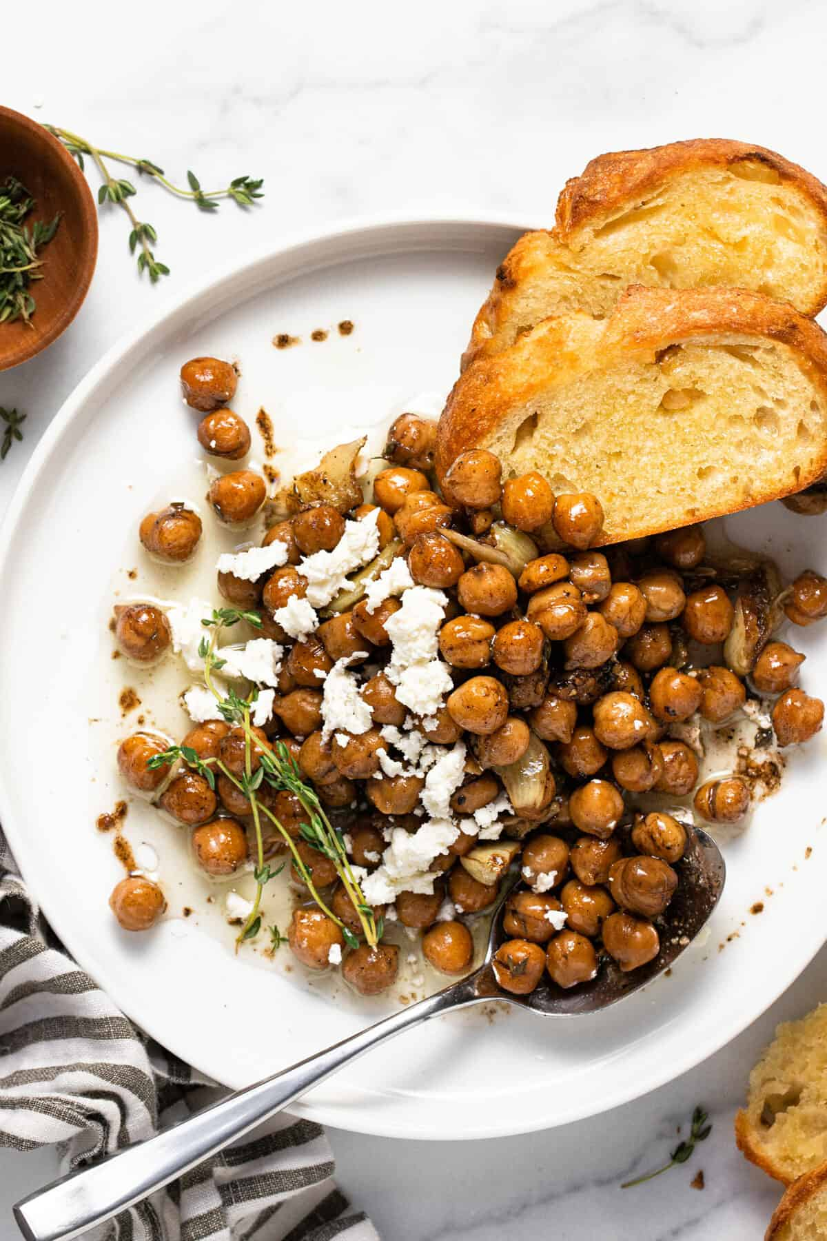 White plate filled with braised chickpeas and a couple slices of crusty bread