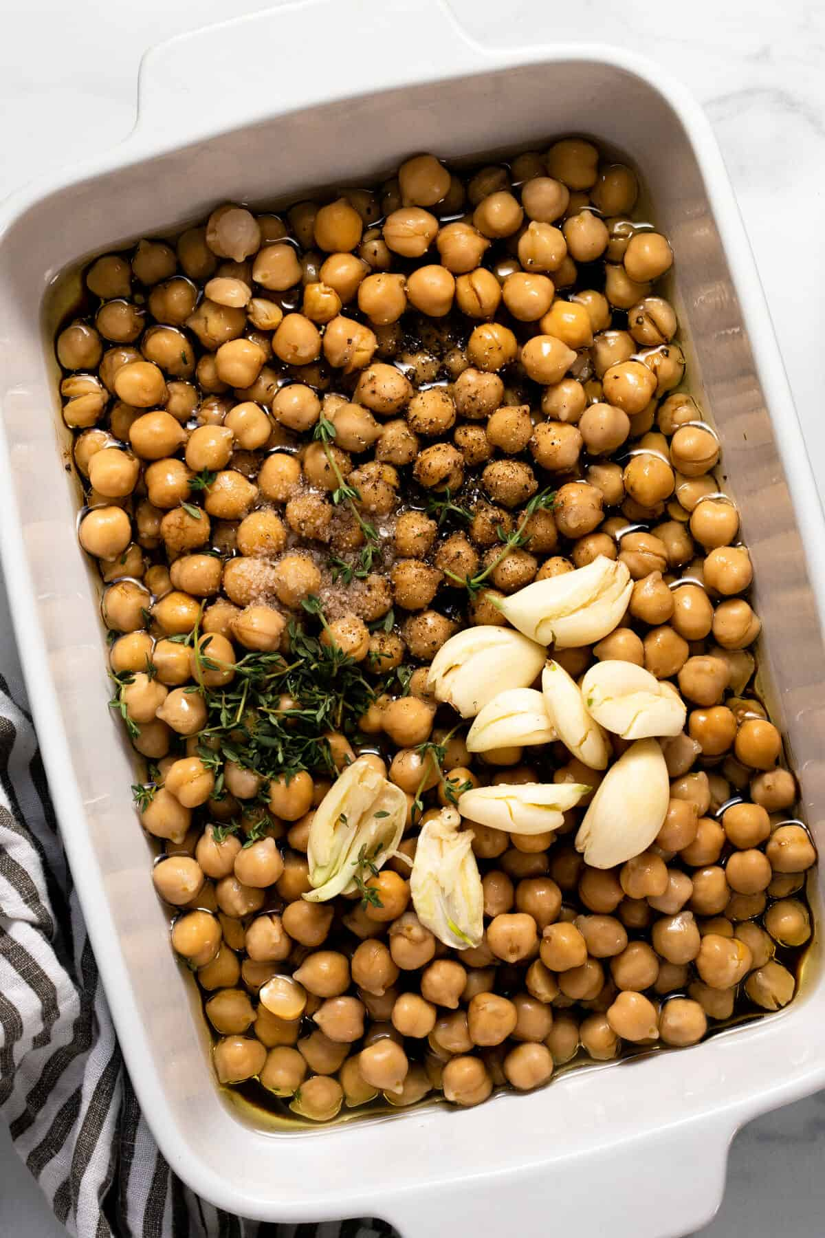 Ingredients to make braised chickpeas in a large white baking dish