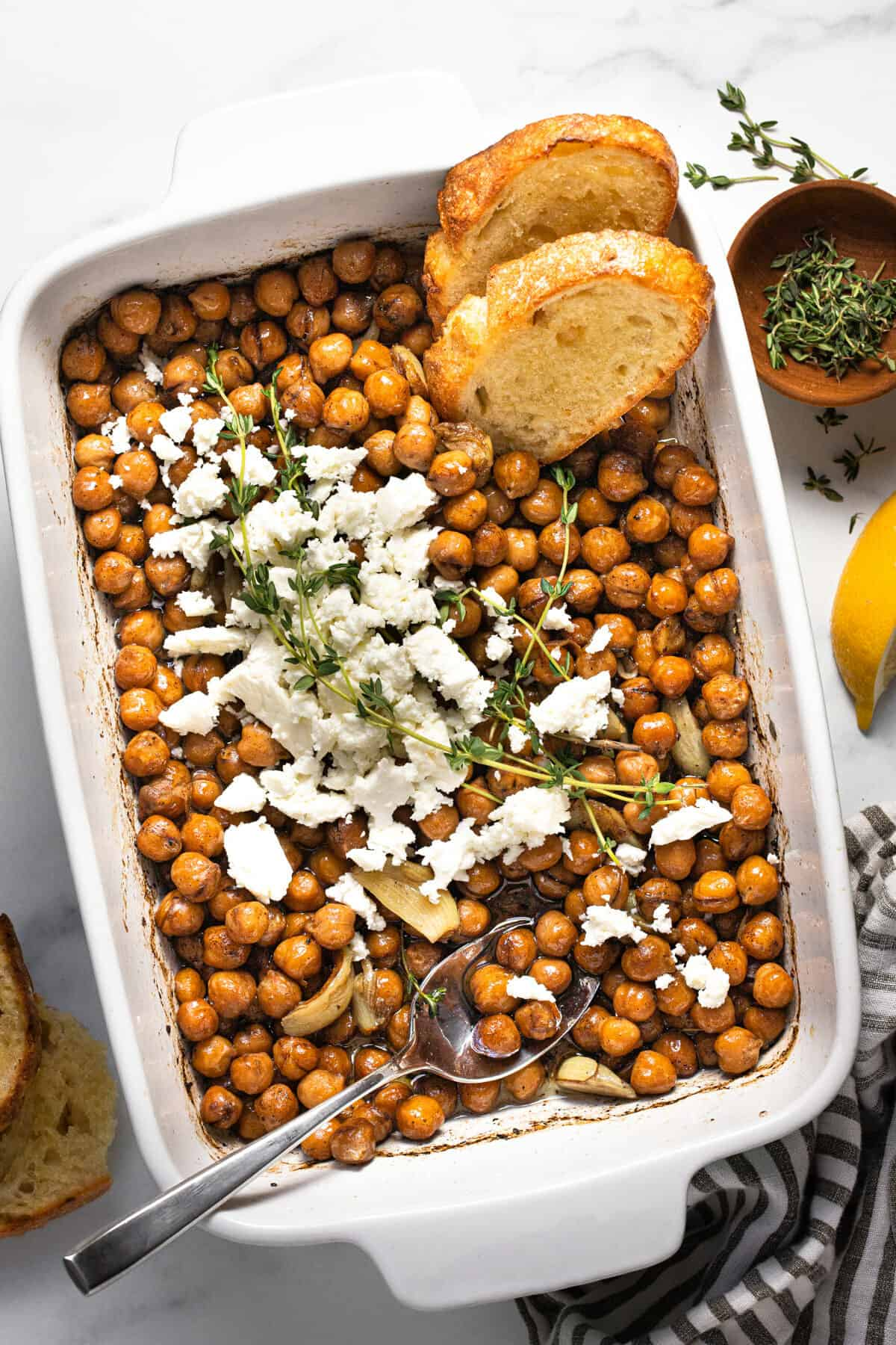 Large baking dish filled with braised chickpeas topped with feta and herbs