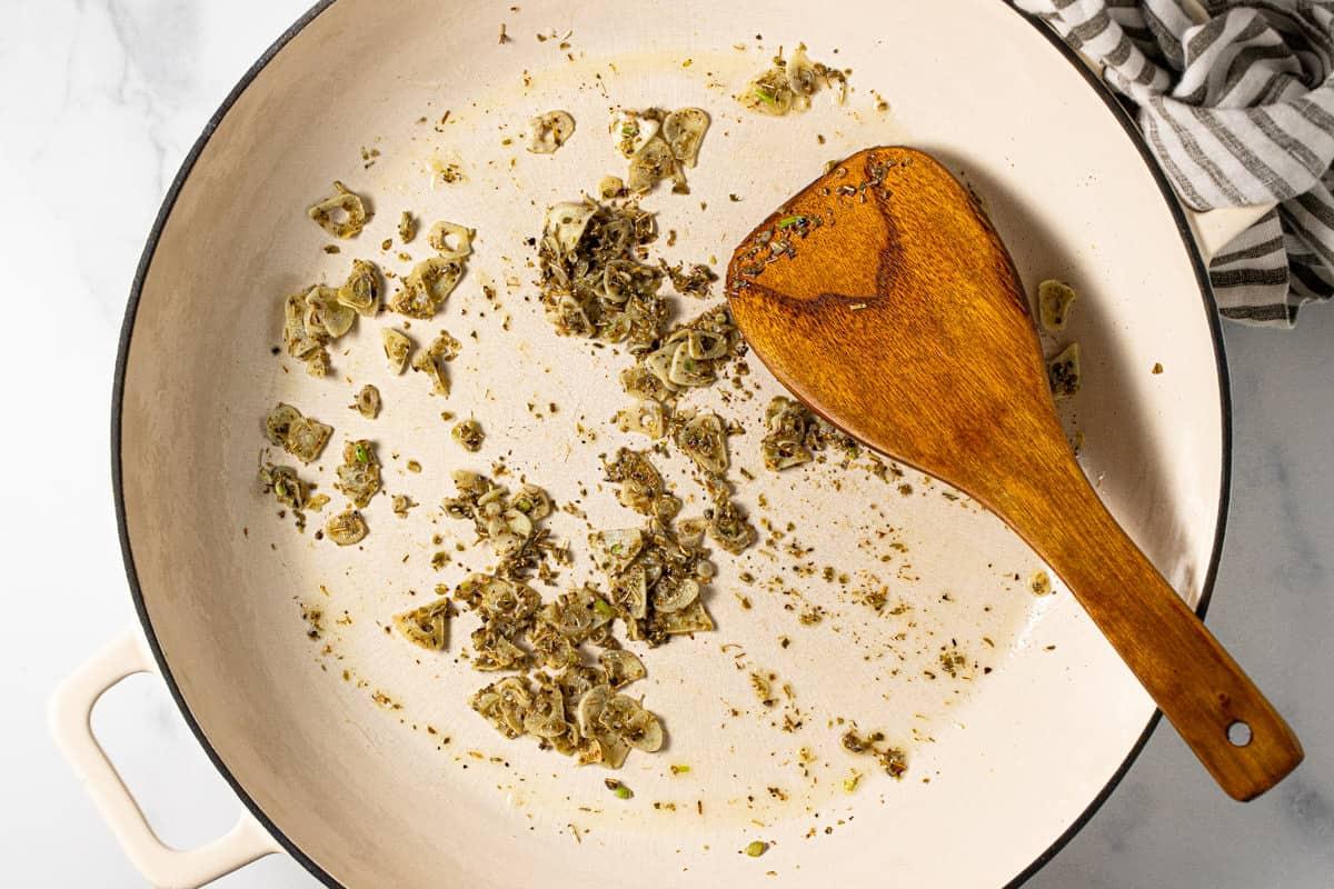 Large pan with sautéed garlic and dried herbs