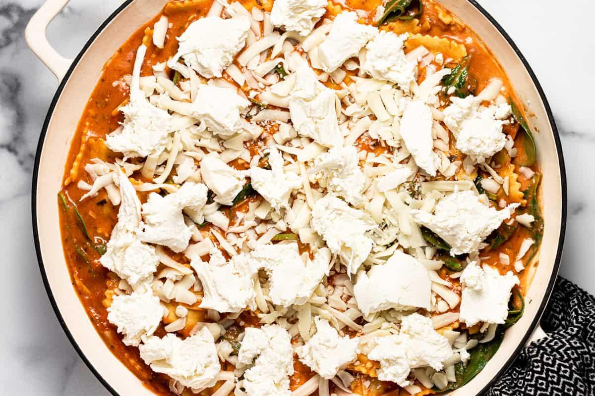 Large white pan filled with ingredients to make baked ravioli casserole