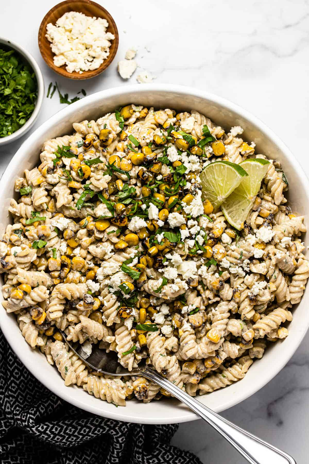 Overhead shot of a white bowl filled with Mexican street corn pasta salad garnished with fresh cilantro