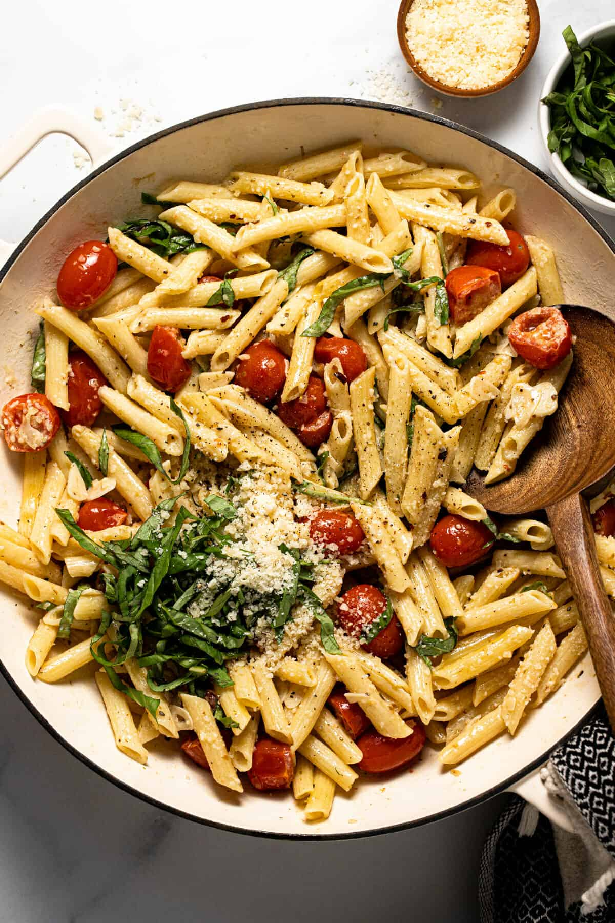 Large white pan filled with pasta with tomatoes and garlic white wine sauce