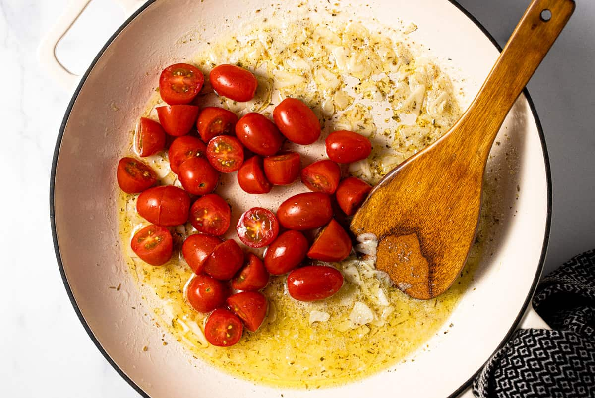 Large white pan filled with butter oil sauteed garlic and tomatoes