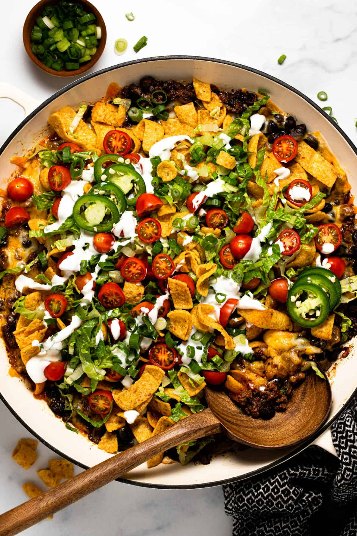 Overhead shot of a large pan filled with walking taco casserole garnished with sour cream