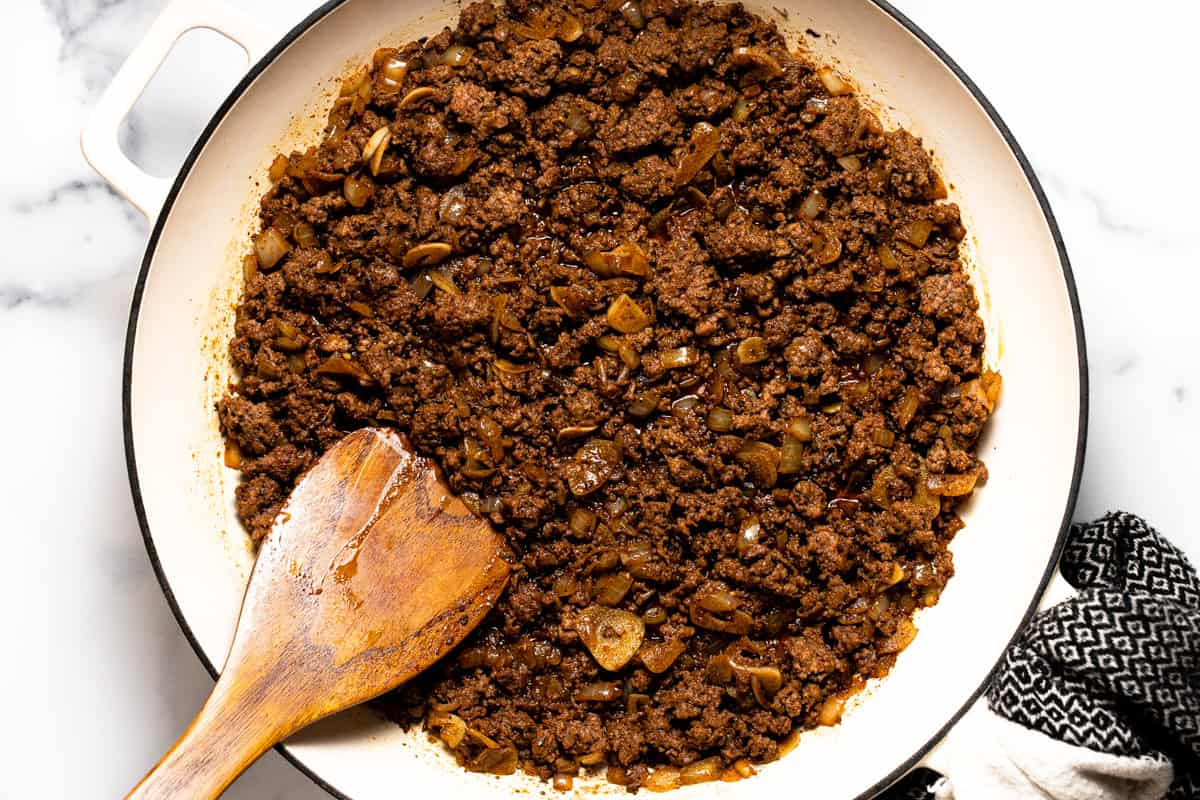 Large pan filled with cooked ground beef and spices