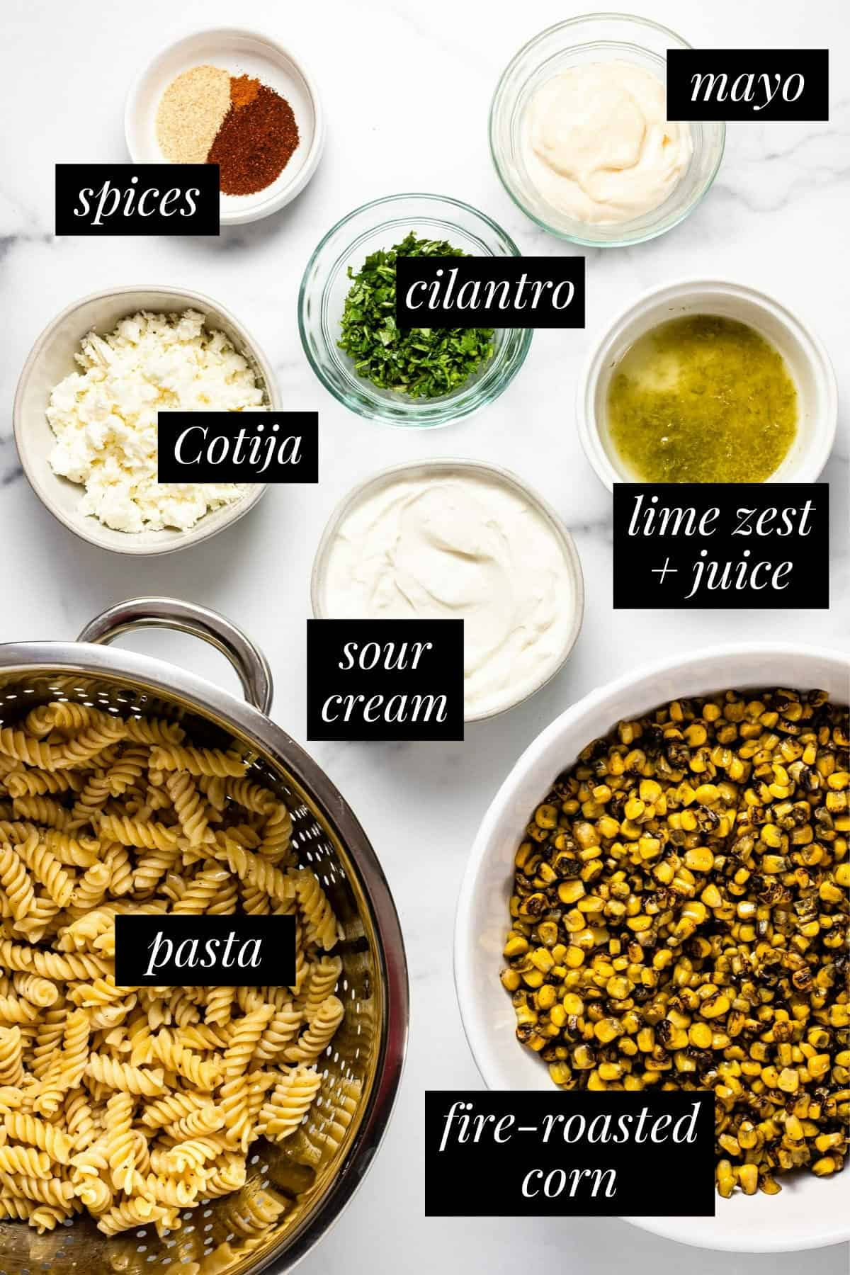 White marble counter top with ingredients to make Mexican street corn pasta salad