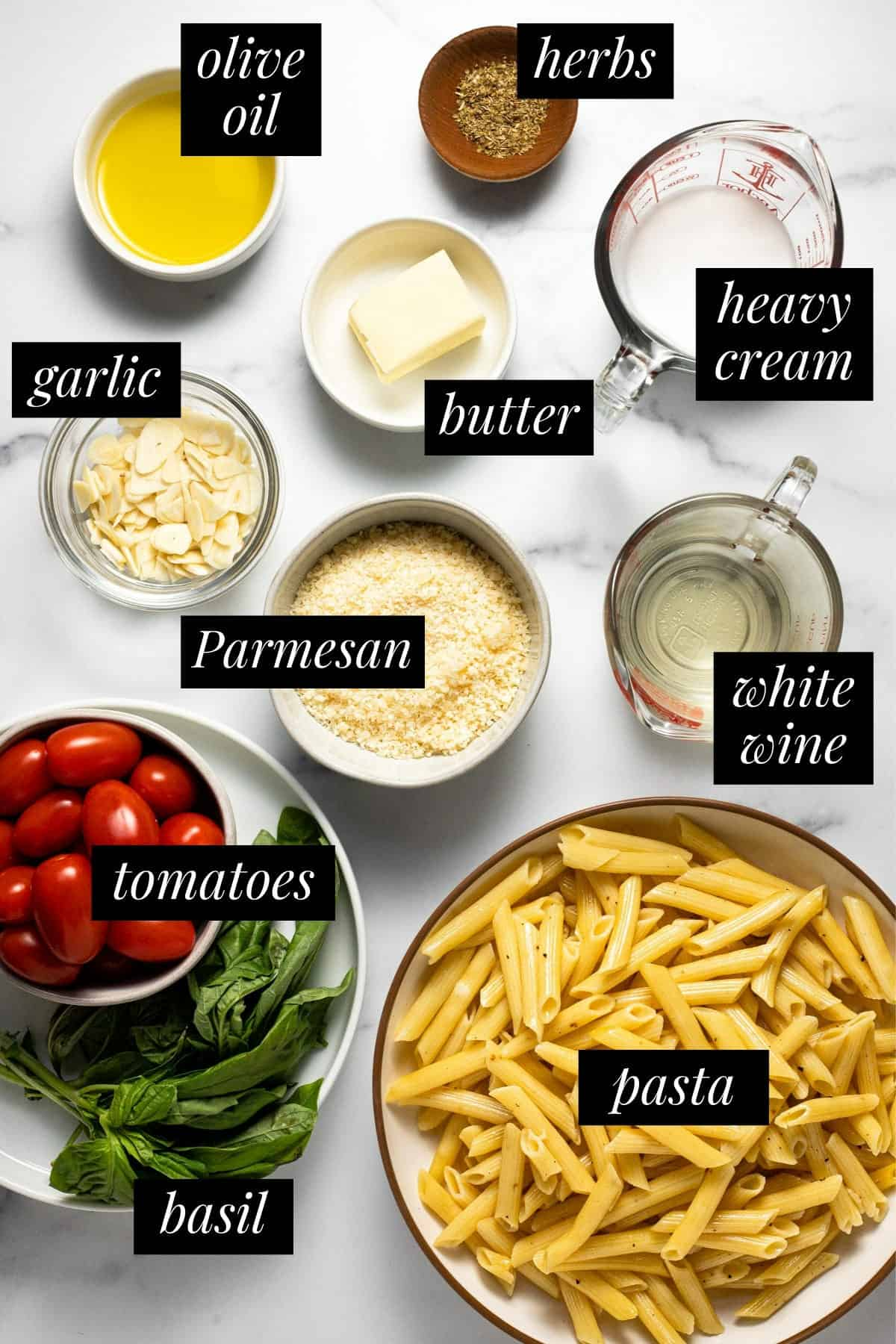 White marble counter top filled with ingredients to make garlic tomato pasta