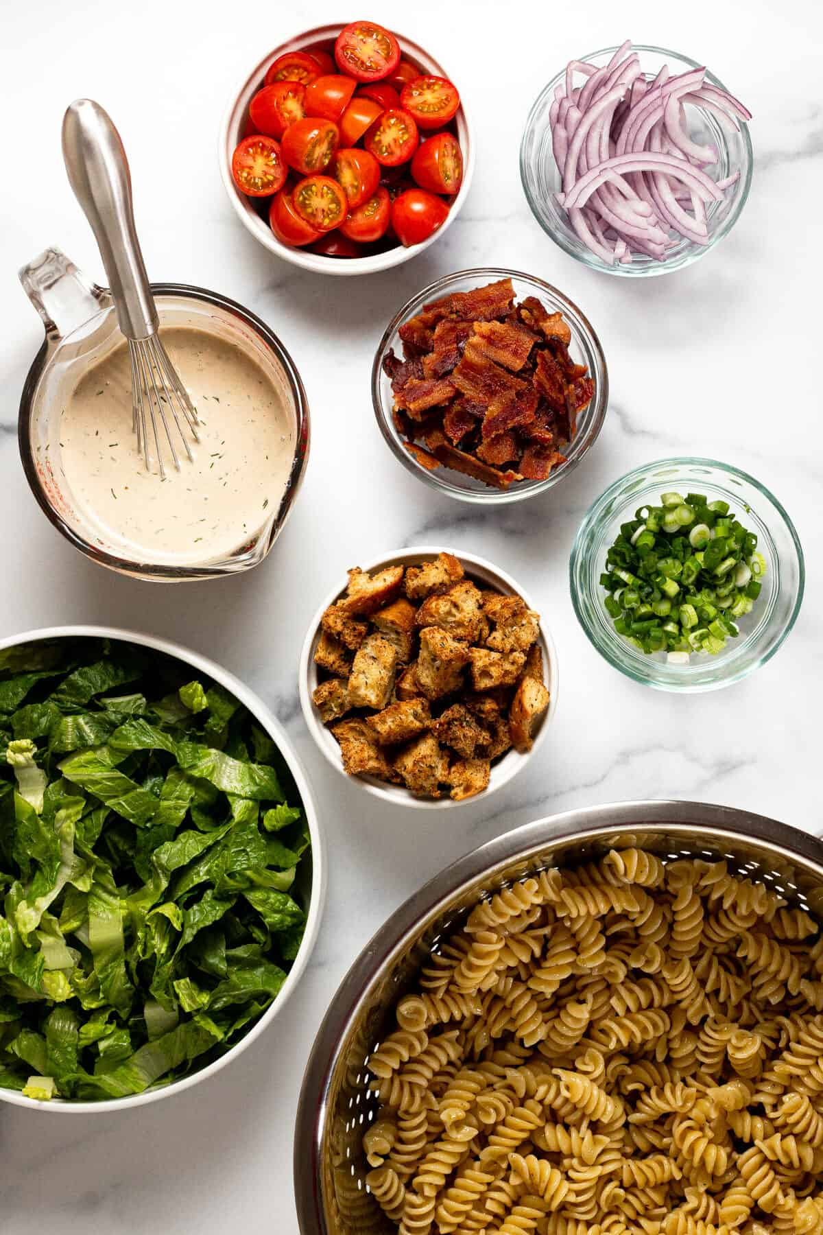White marble counter top with ingredients to make BLT pasta salad