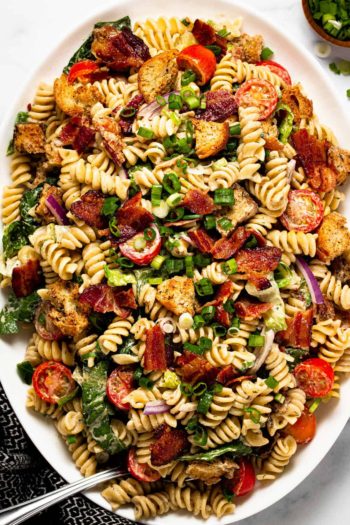 Large white platter filled with BLT pasta salad garnished with green onion