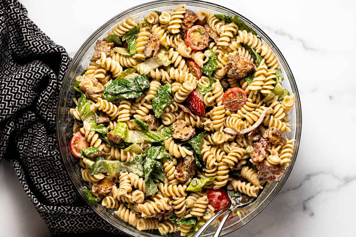 Large glass bowl filled with ingredients to make BLT pasta salad