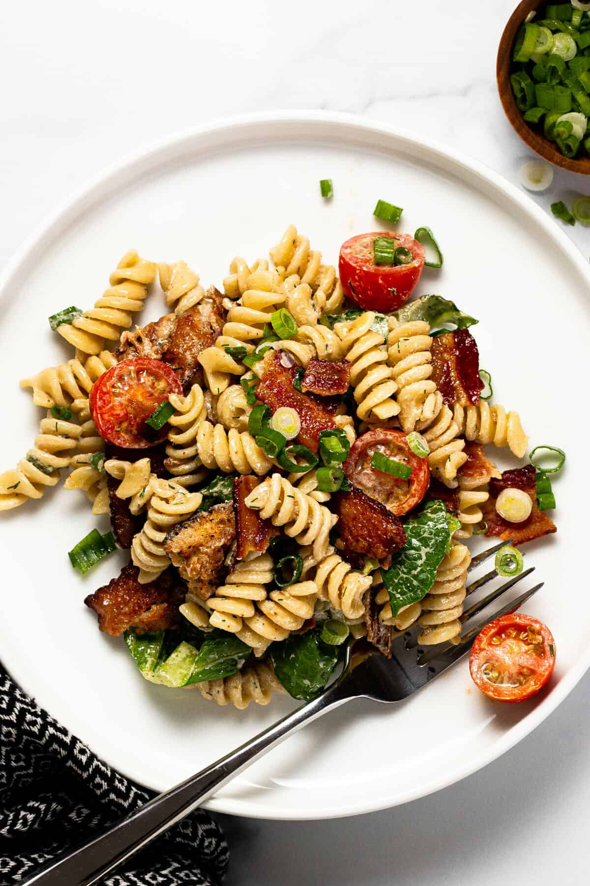 Large white plate filled with BLT pasta salad garnished with green onion