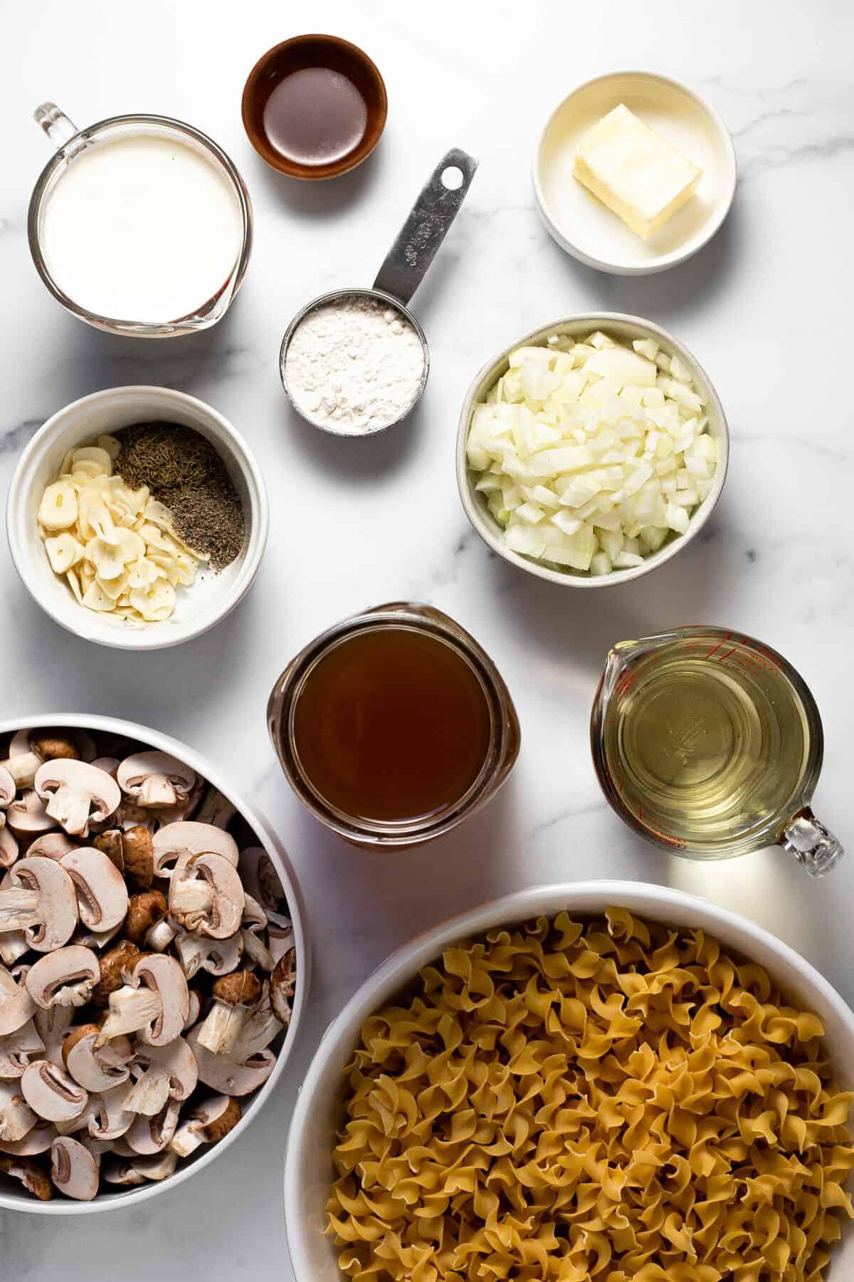 White marble counter top with ingredients to make vegetarian mushroom stroganoff