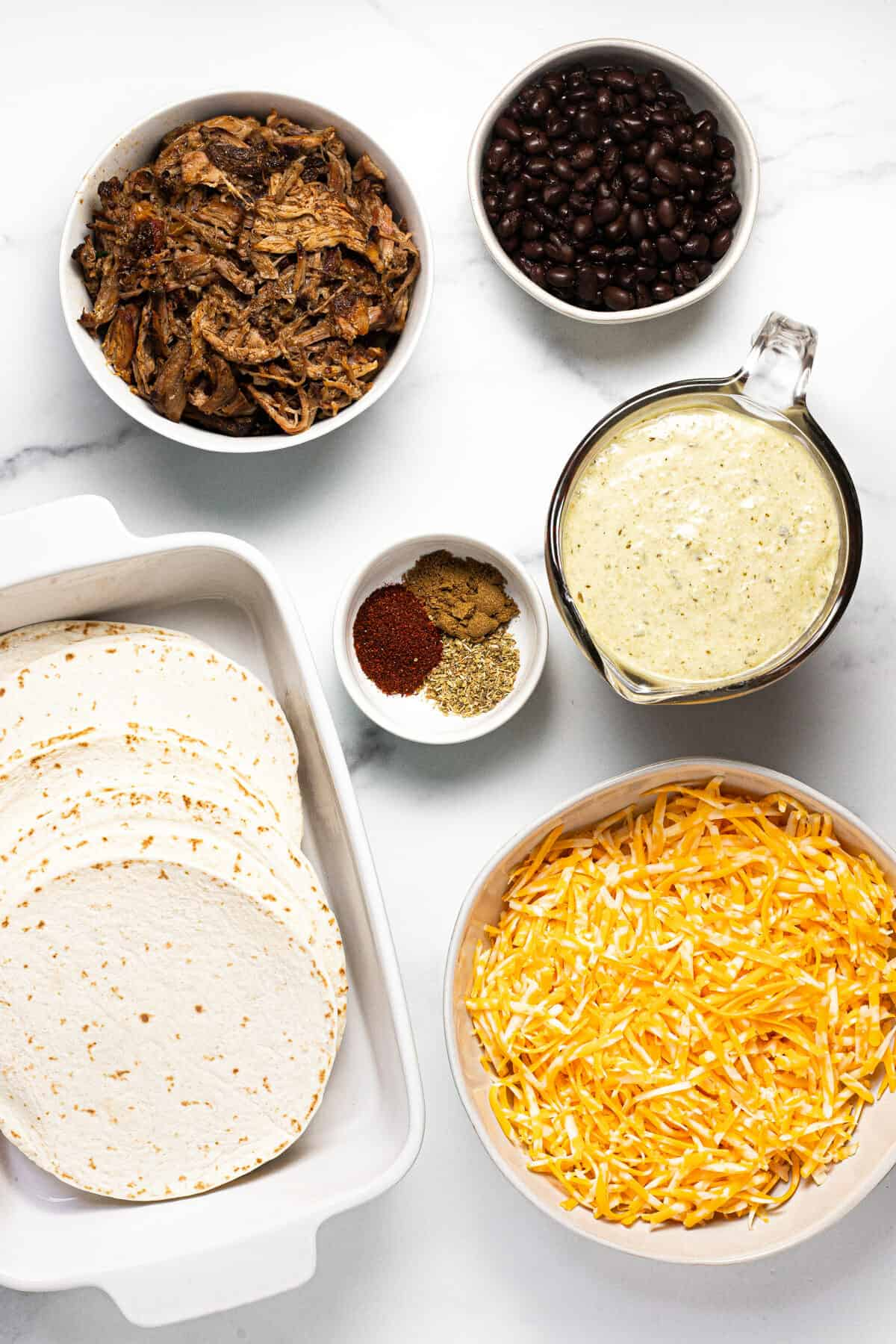 White marble counter top filled with ingredients to make pork enchiladas