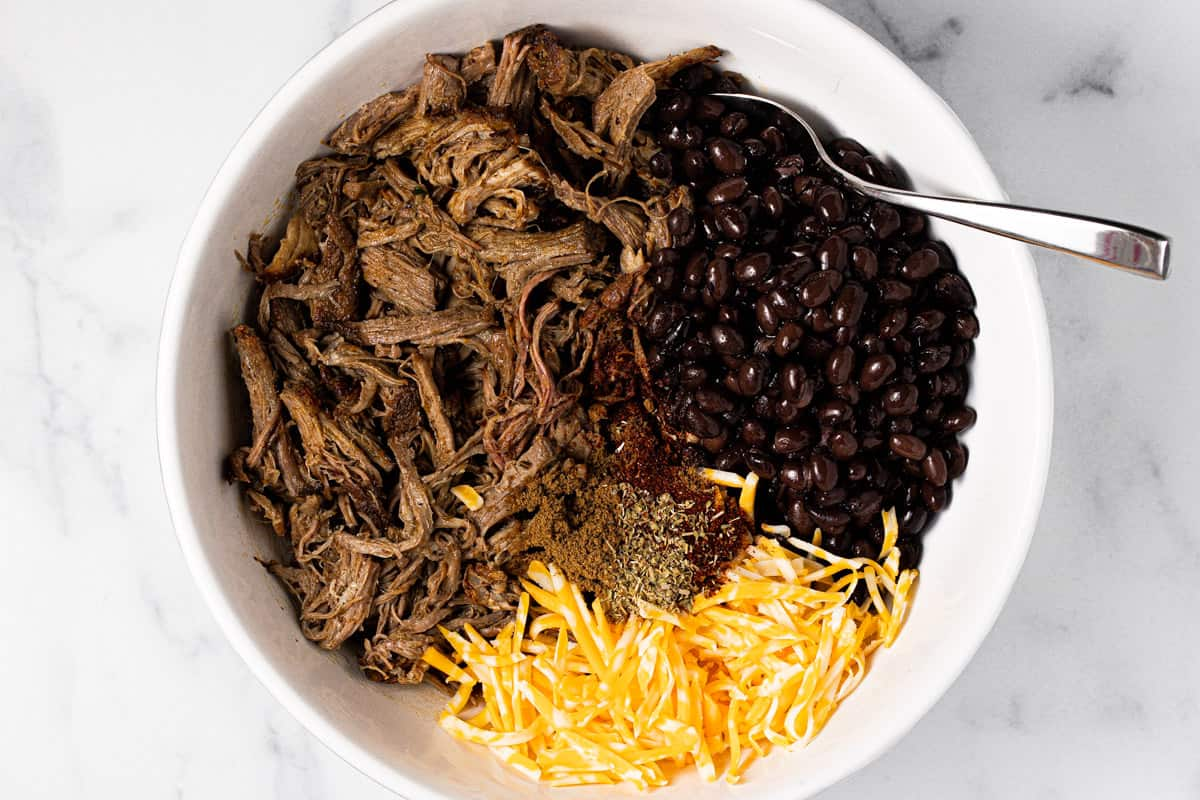 Large white bowl with pulled pork black beans and cheese to fill enchiladas