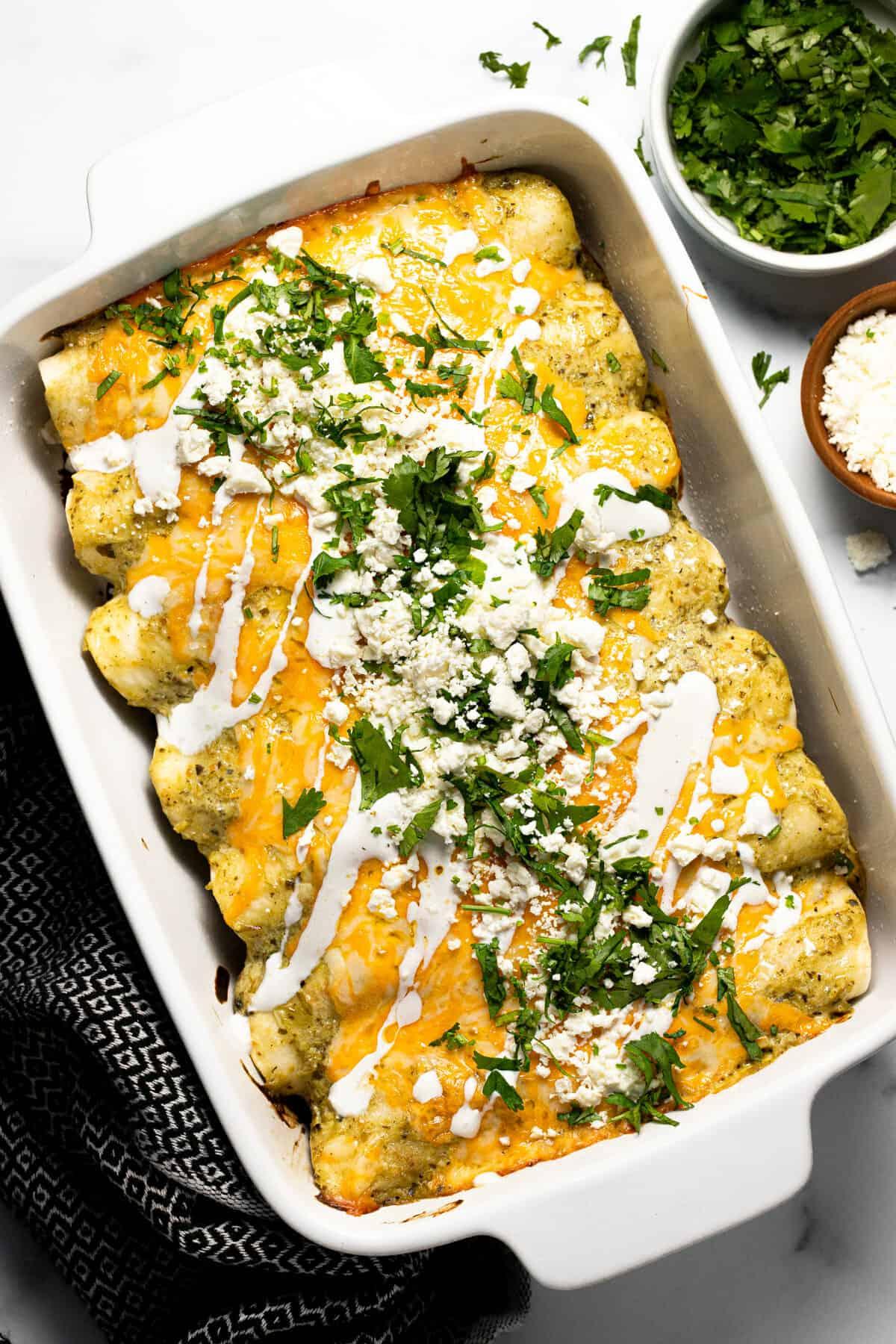 White baking dish filled with pulled pork carnitas enchiladas