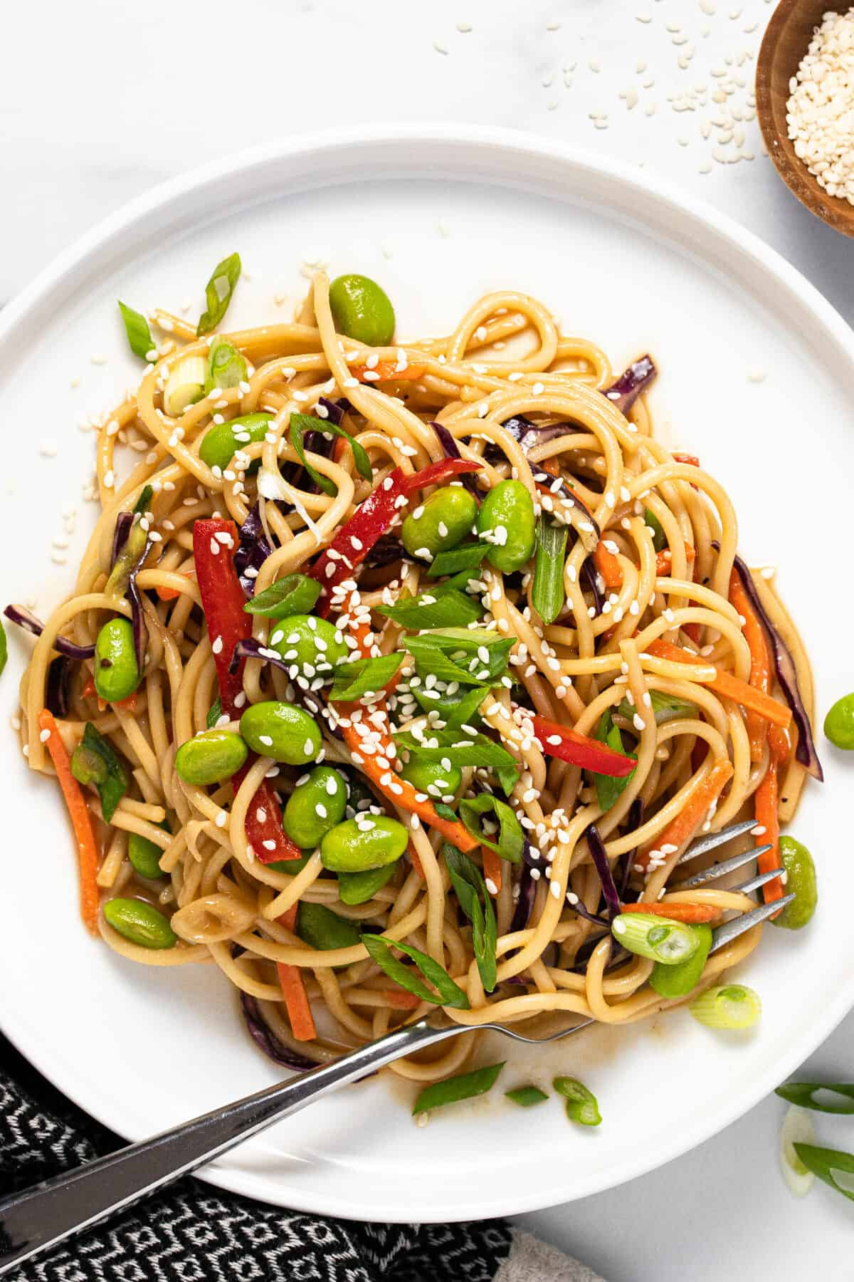 Large white plate filled with sesame noodle salad garnished with green onions