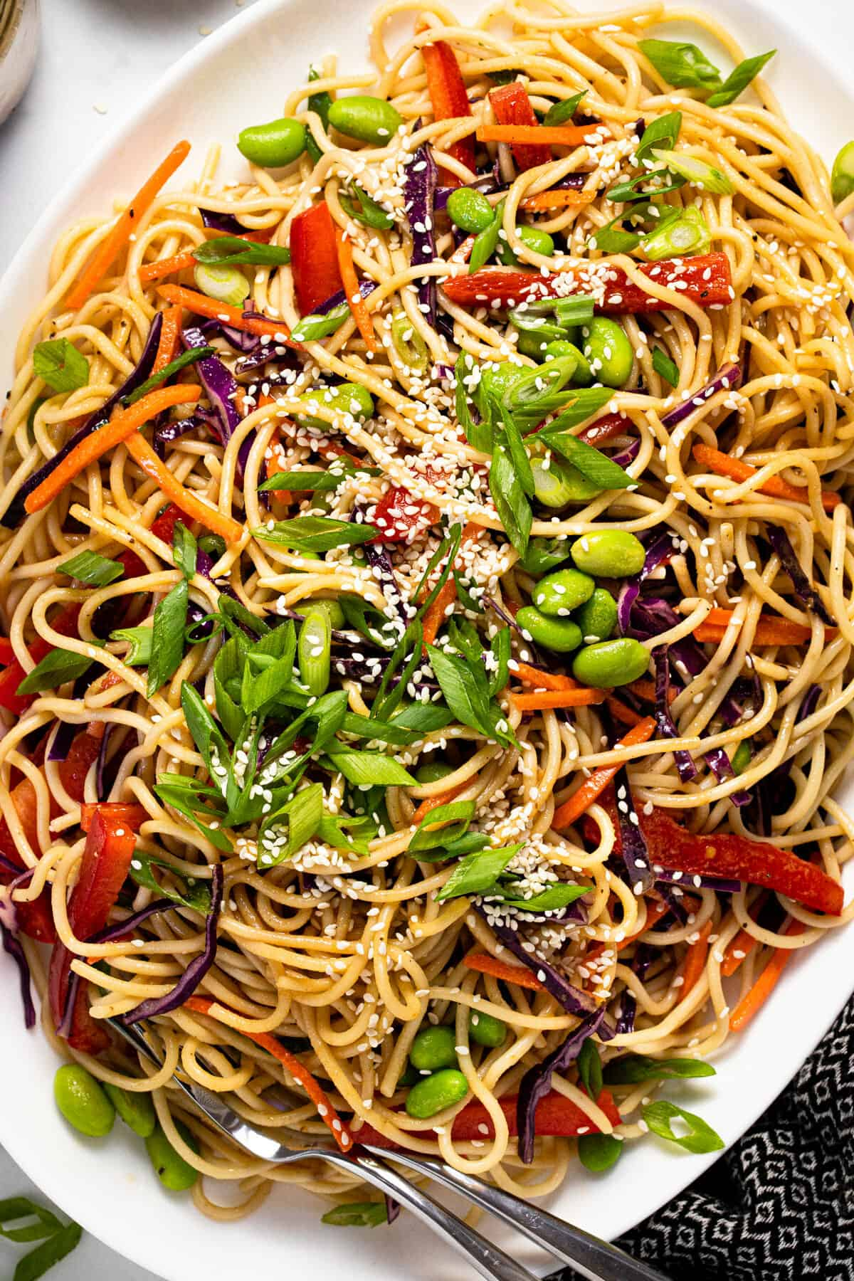 Large white serving platter filled with sesame noodle salad garnished with green onions