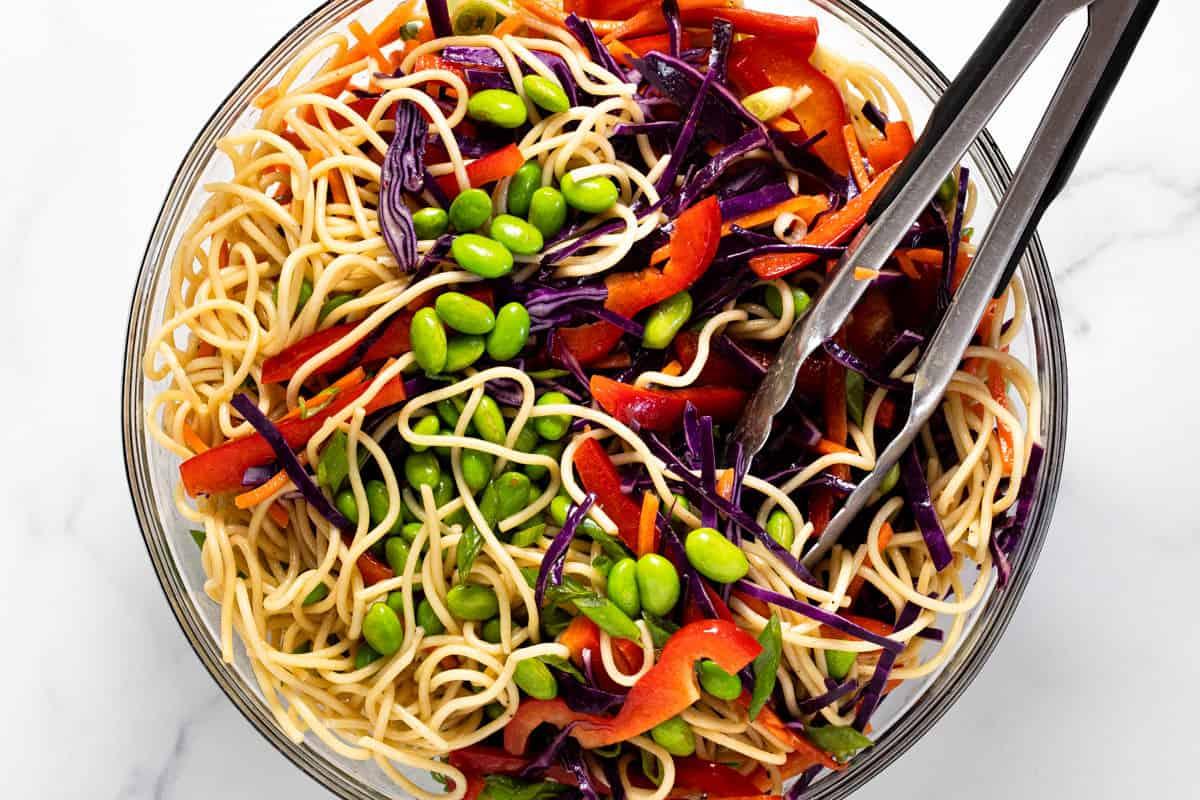 Large glass bowl filled with ingredients to make sesame noodle salad