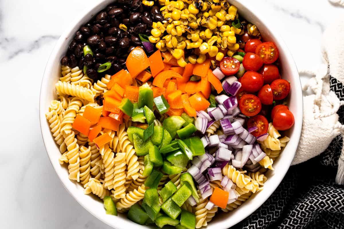 Large white bowl filled with ingredients to make taco pasta salad