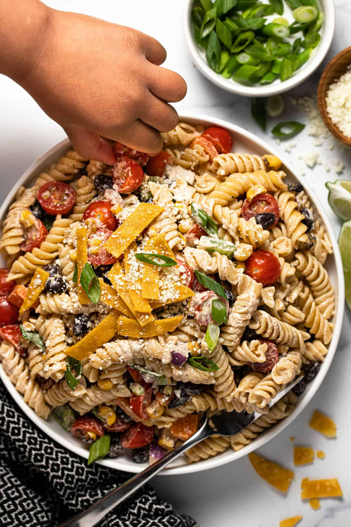 Small hand reaching for a tomato that's in a large white bowl of taco pasta salad