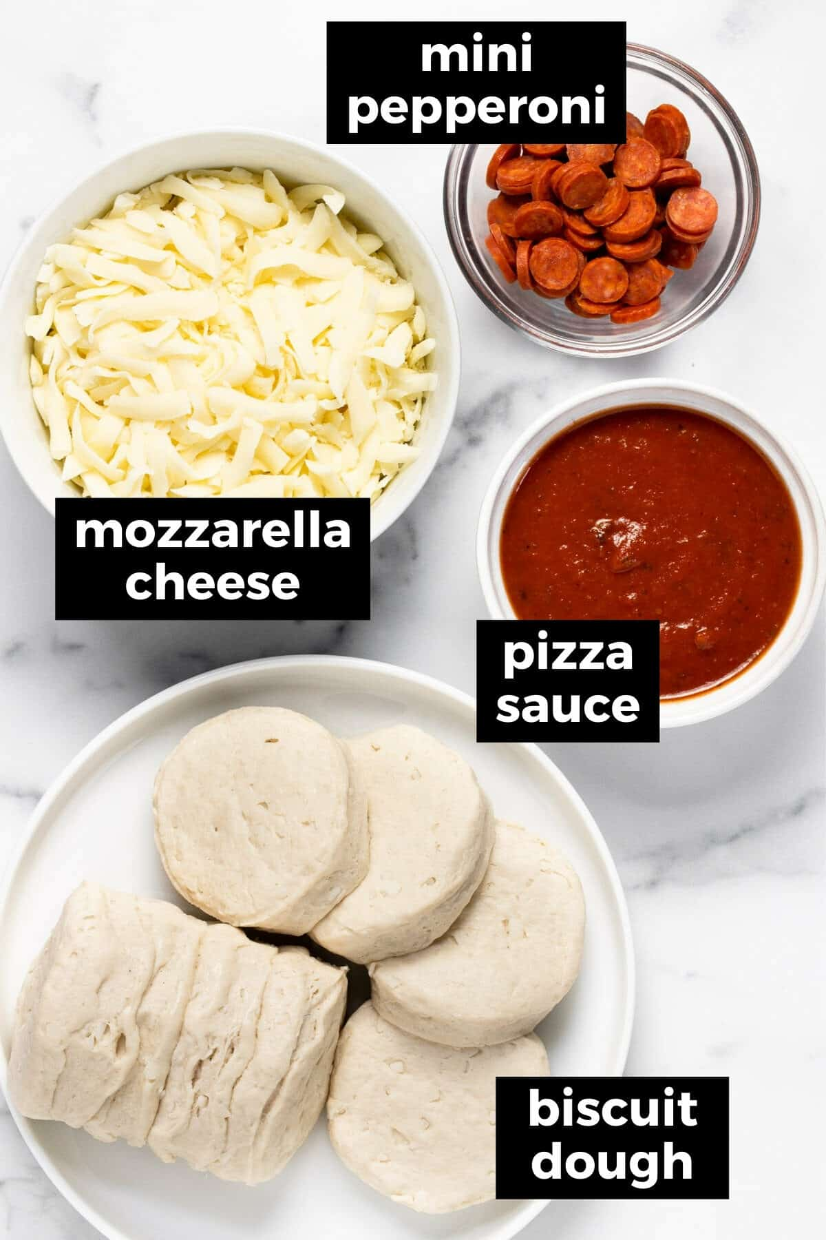 White marble counter top with ingredients to make homemade personal pizzas