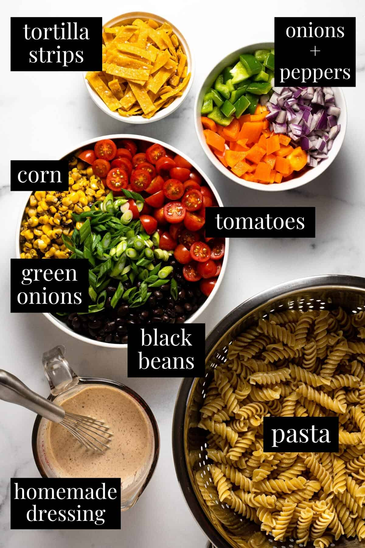 White marble counter top with ingredients to make taco pasta salad