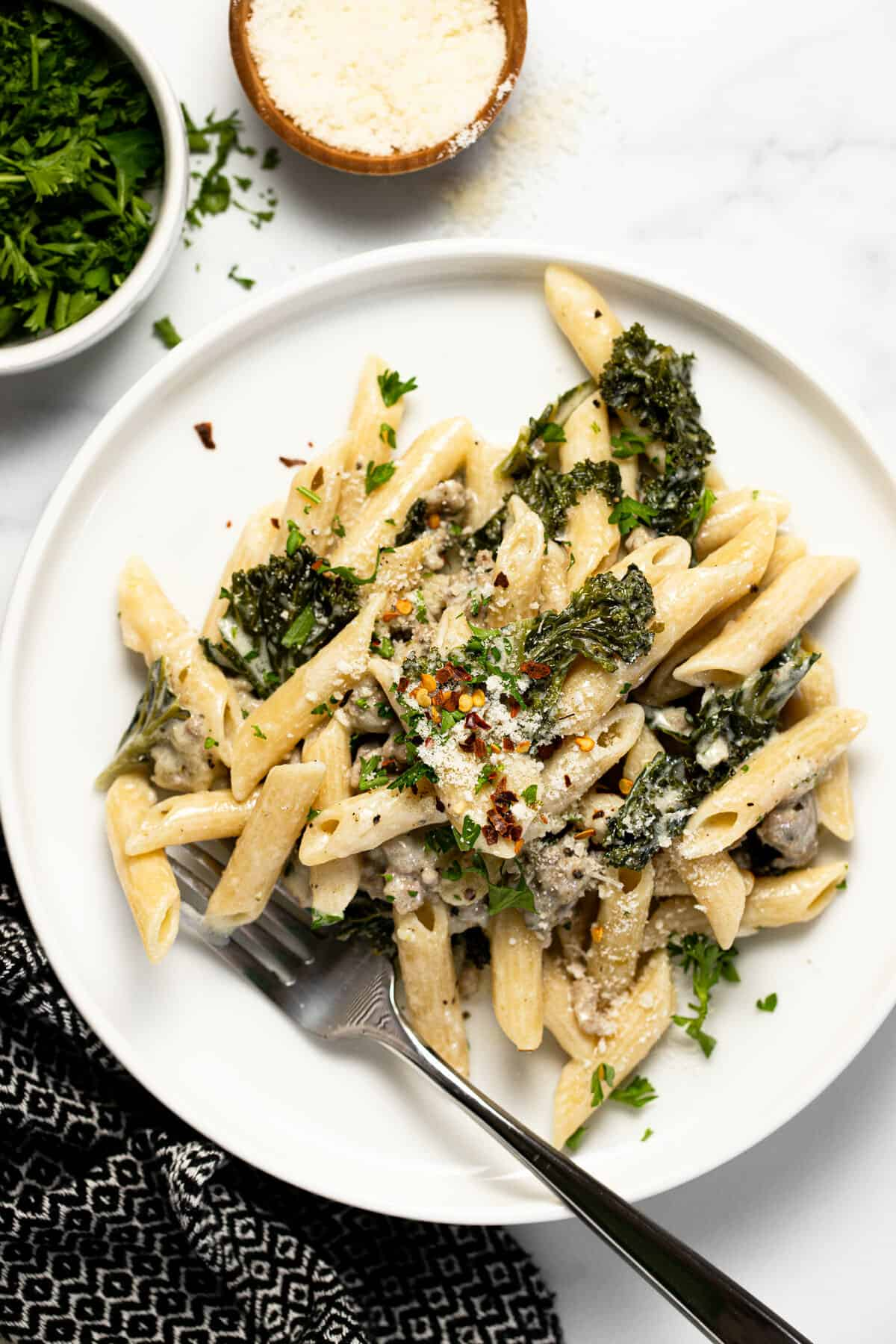 White plate filled with penne pasta in cream sauce with sausage and kale
