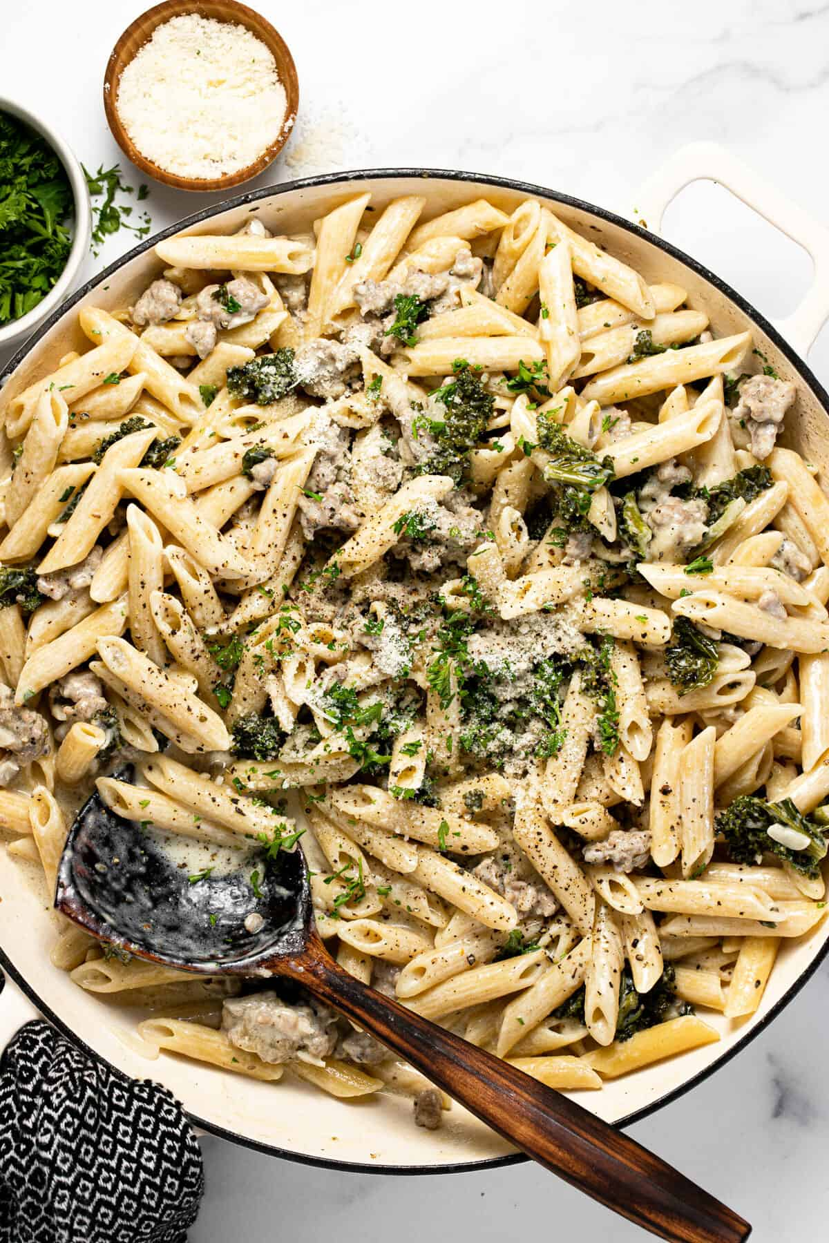 Large white pan filled with ingredients to make Italian sausage pasta garnished with chopped parsley