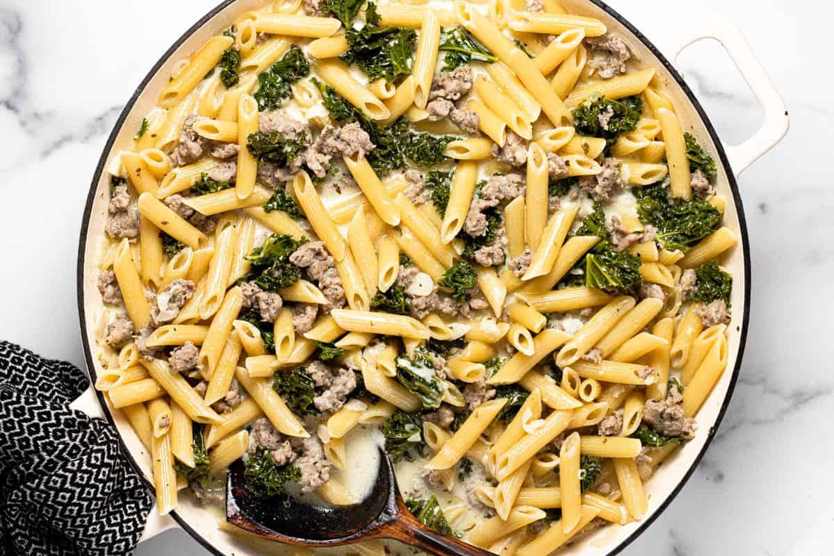 Large white pan with ingredients to make sausage kale pasta