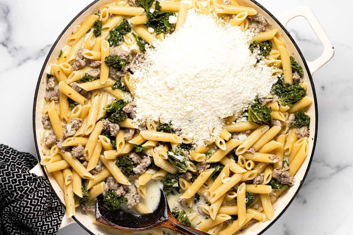 Large white pan filled with ingredients to make Italian sausage pasta