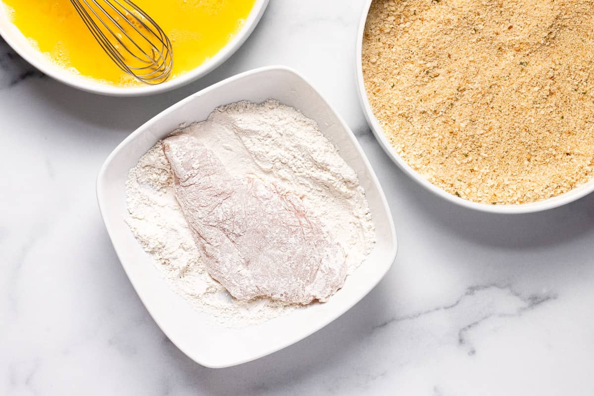 Chicken breast in a shallow bowl of flour