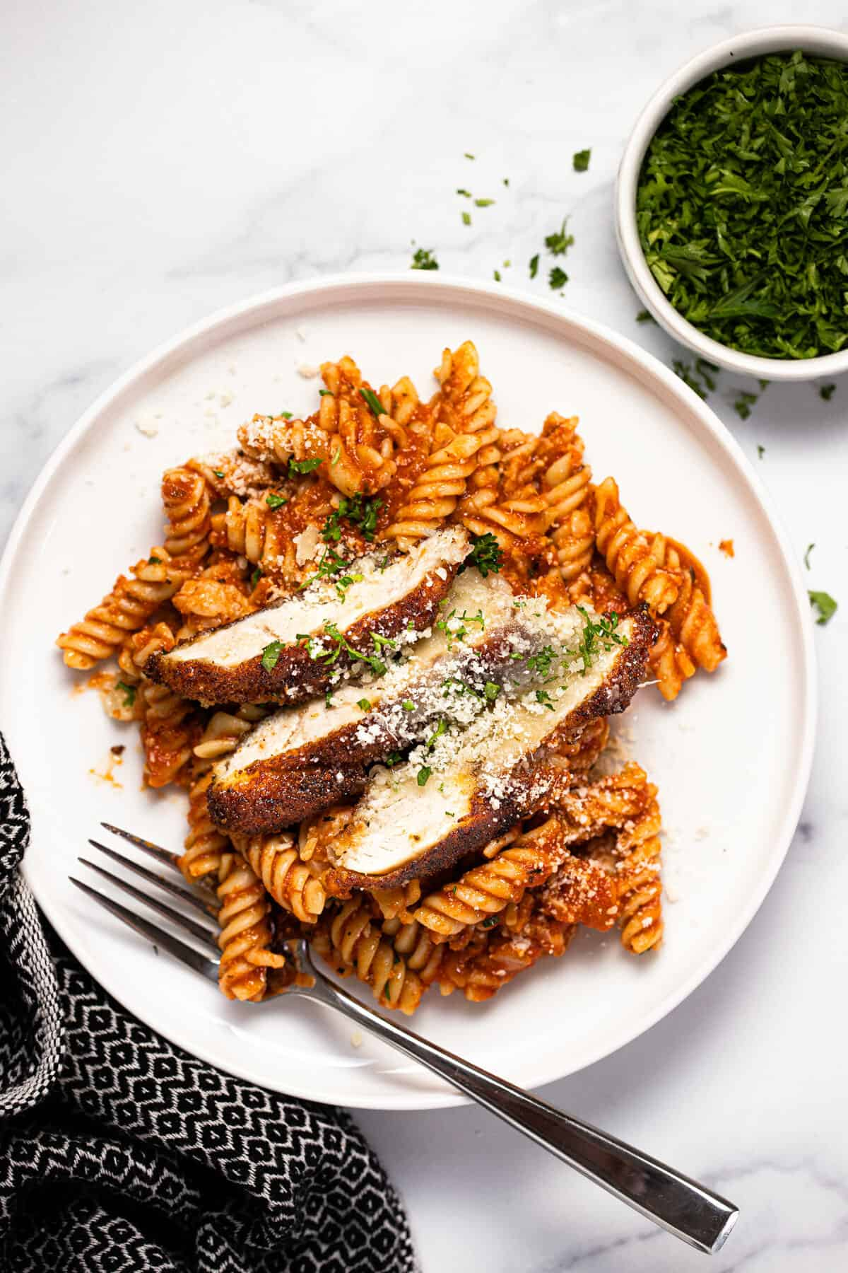 White plate filled with chicken Parmesan casserole garnished with fresh parsley