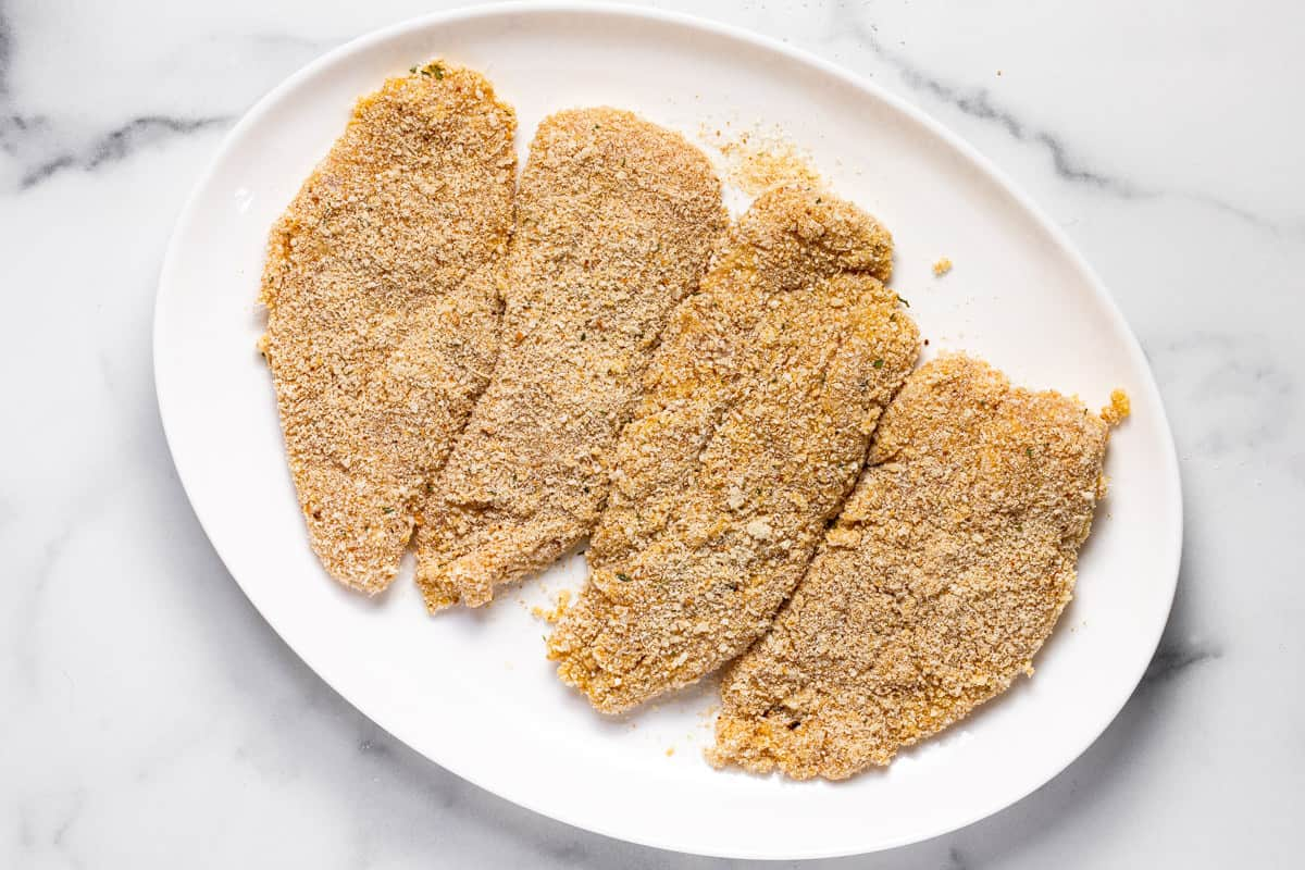 Large white platter filled with breaded Parmesan chicken breast
