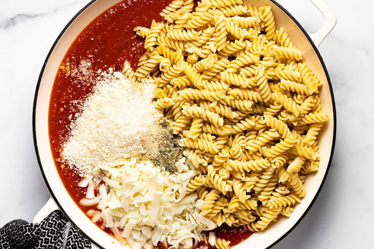 Pasta spaghetti sauce and cheese in a large white pan