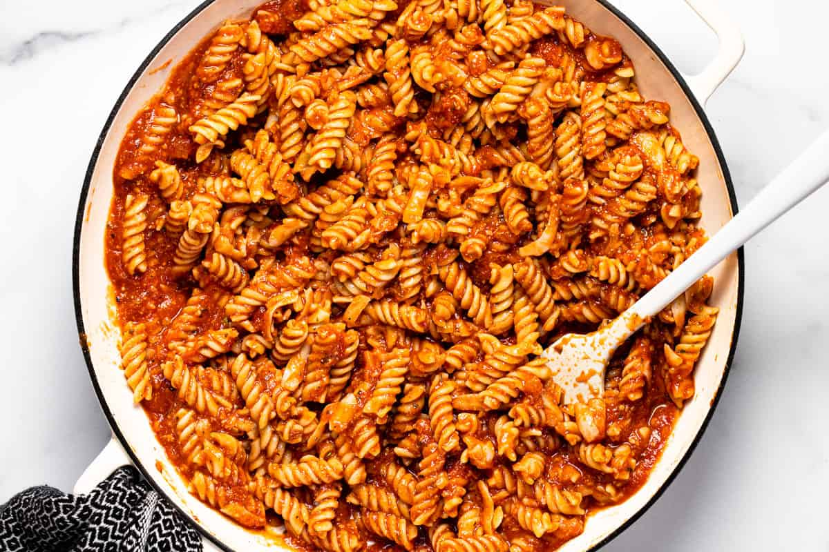Rotini pasta coated in red sauce in a large white pan