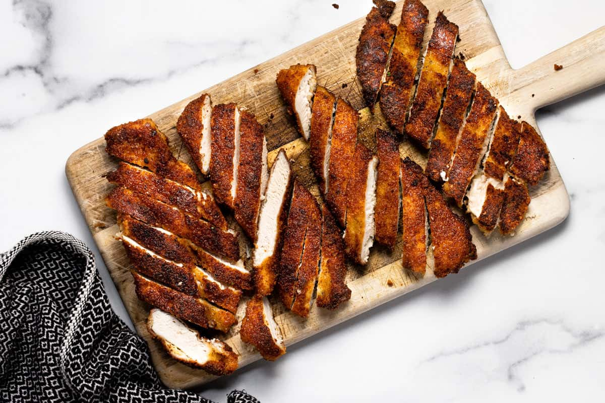 Fried chicken sliced into strips on a wooden cutting board