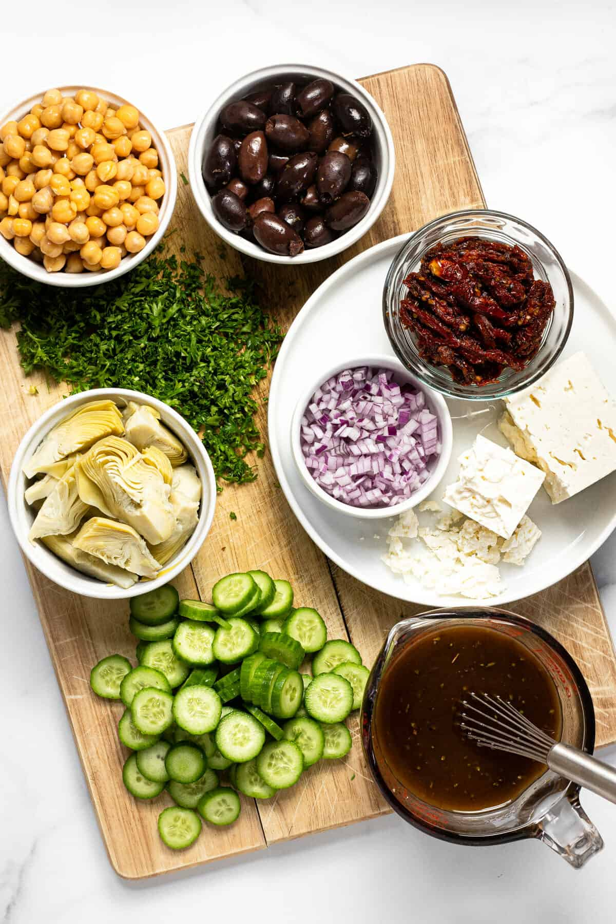 Wooden cutting board with ingredients to make Greek orzo salad on it