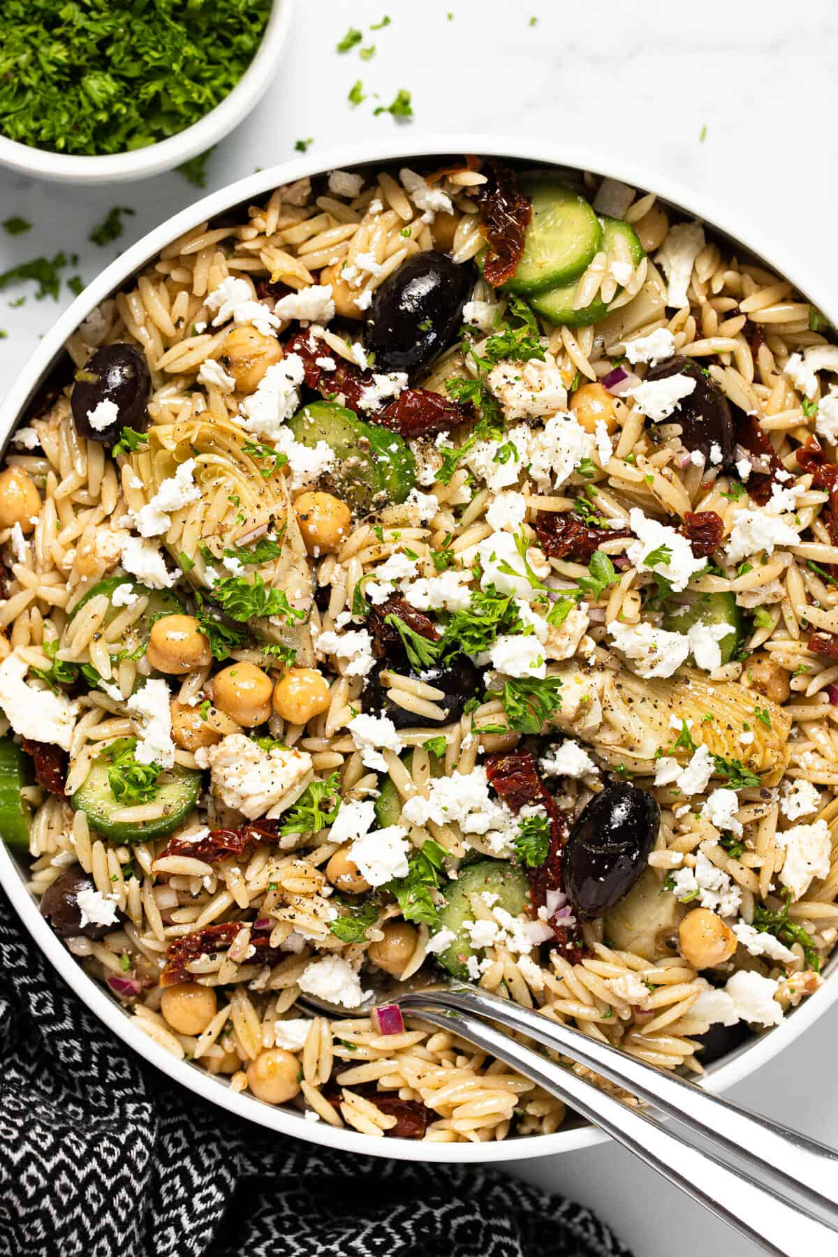 Large white bowl filled with Greek pasta salad garnished with parsley