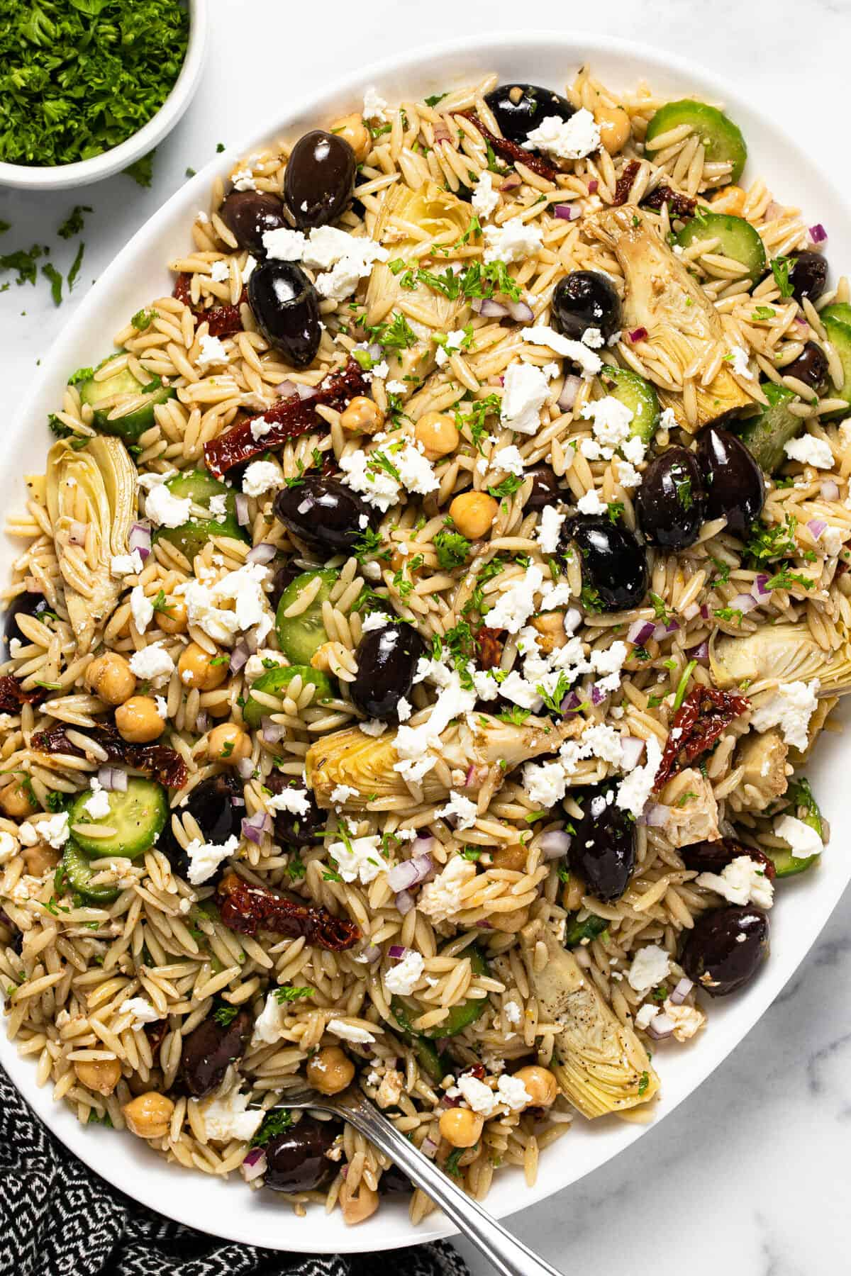 Large white platter filled with Greek orzo pasta salad