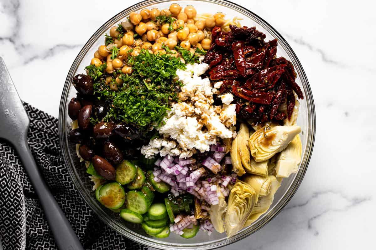 Glass bowl filled with ingredients to make Mediterranean pasta salad