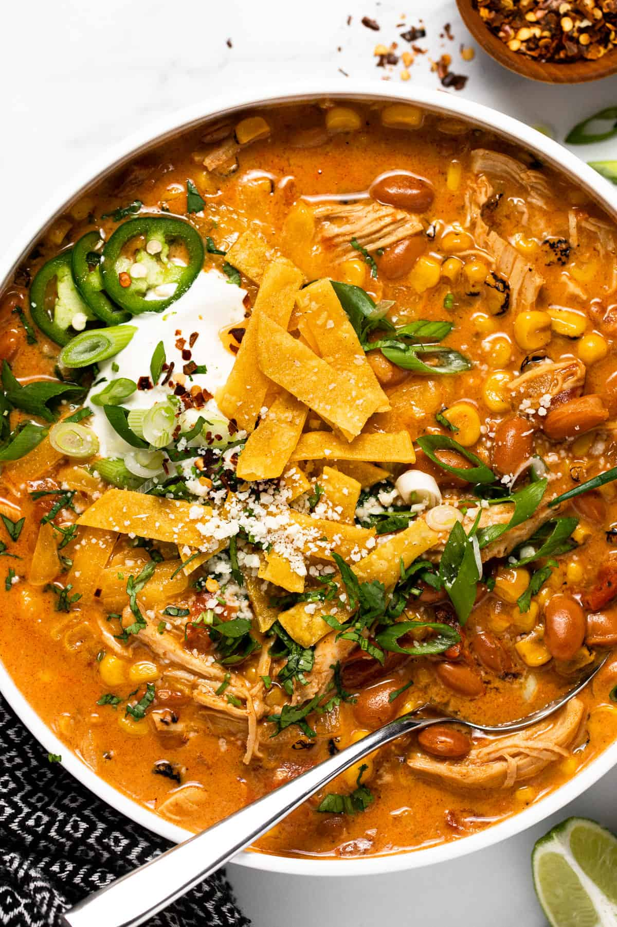 Large white bowl filled with instant pot chicken chili garnished with sour cream and tortilla strips