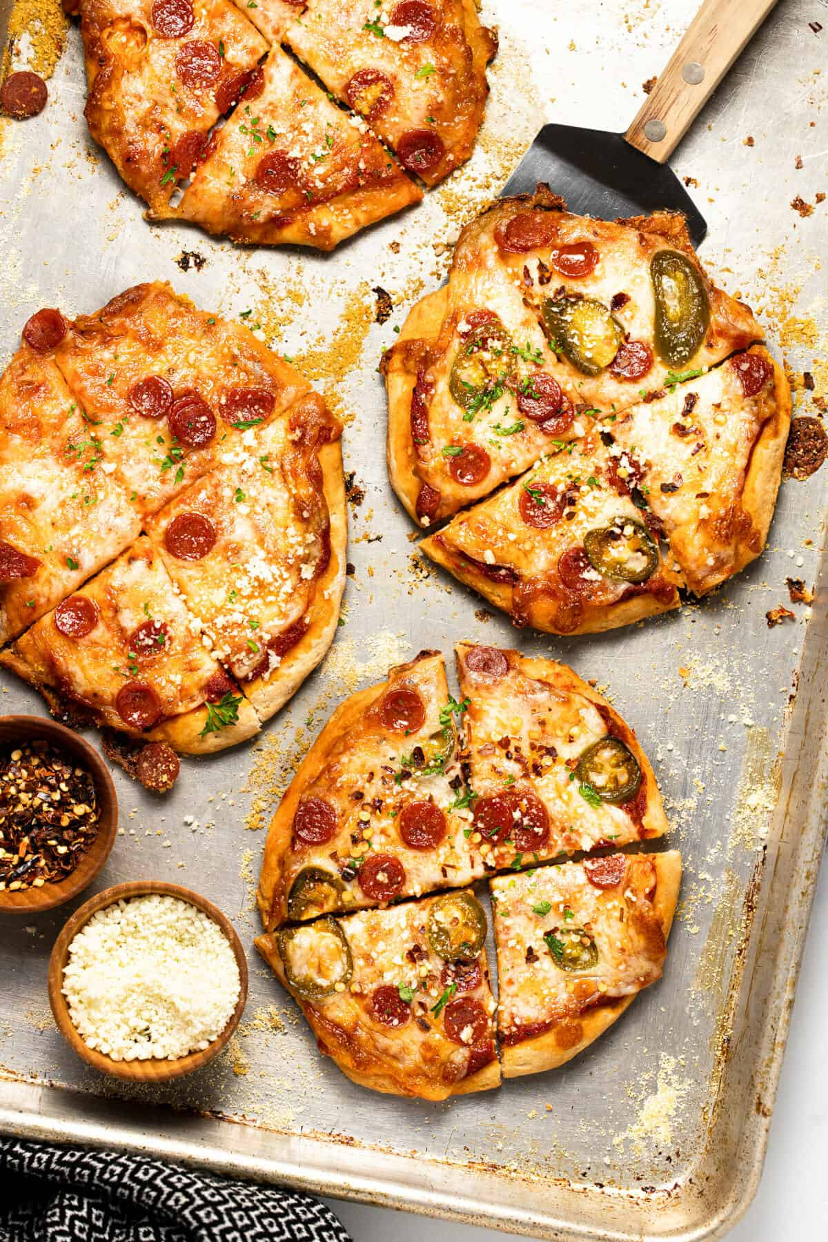 Baking sheet with homemade mini pizzas garnished with grated Parmesan cheese