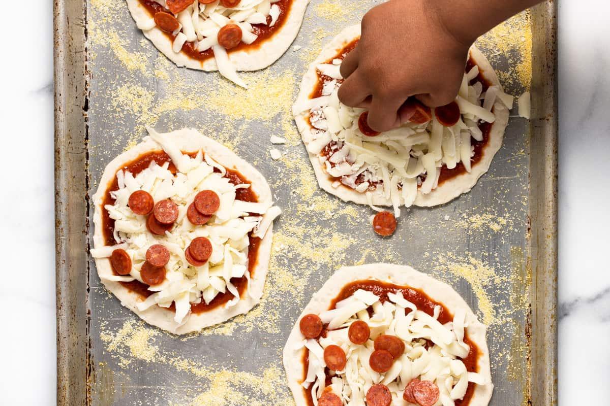 A small hand adding a handful of mini pepperoni to mini pizzas