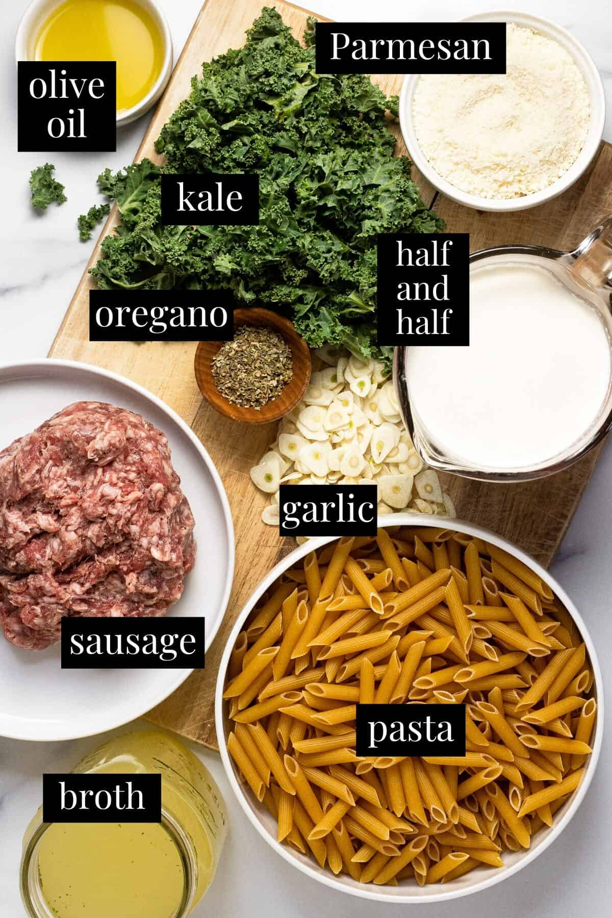 White marble counter top with ingredients to make sausage kale pasta