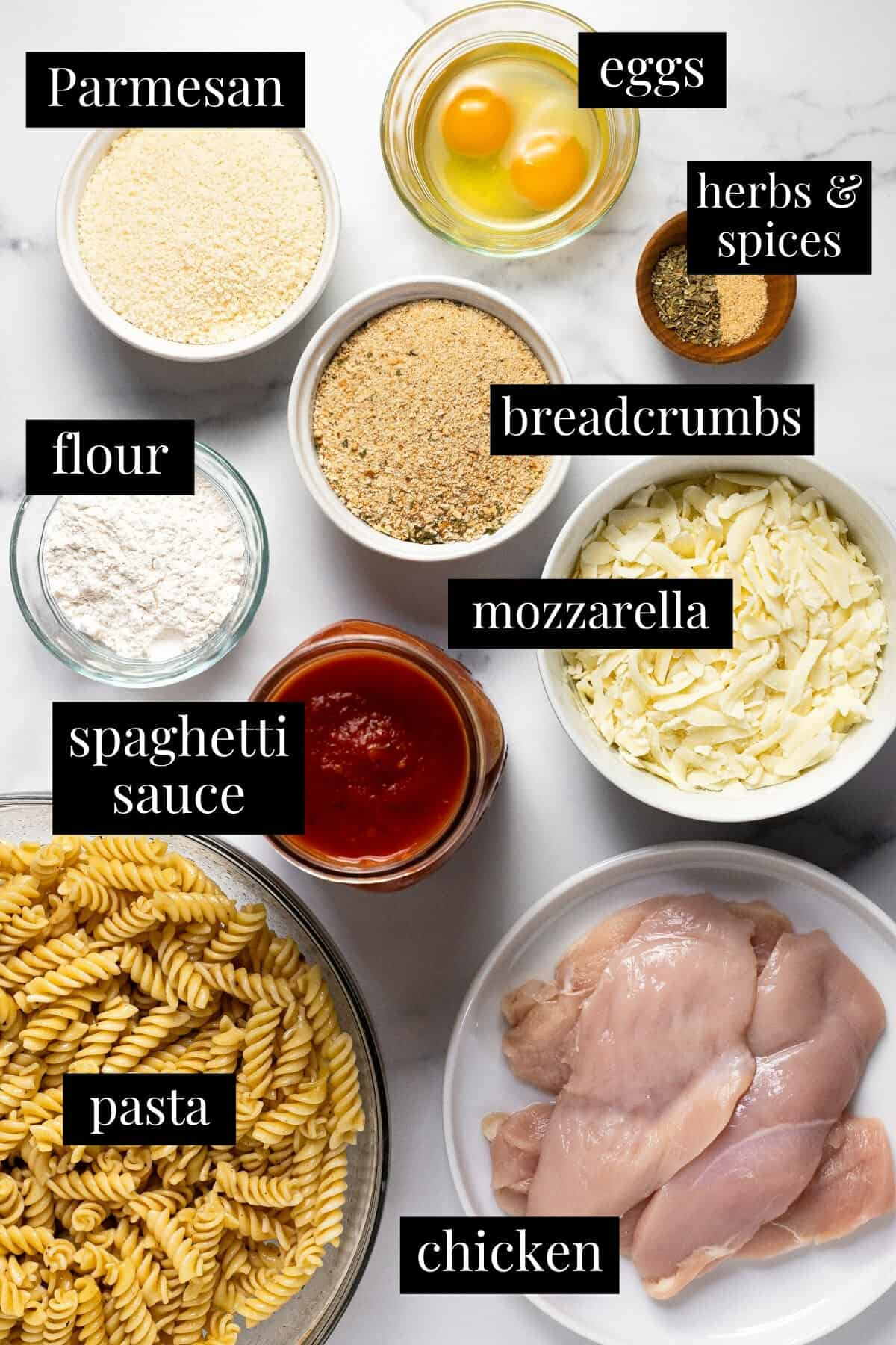 White marble counter top with ingredients to make chicken Parmesan casserole