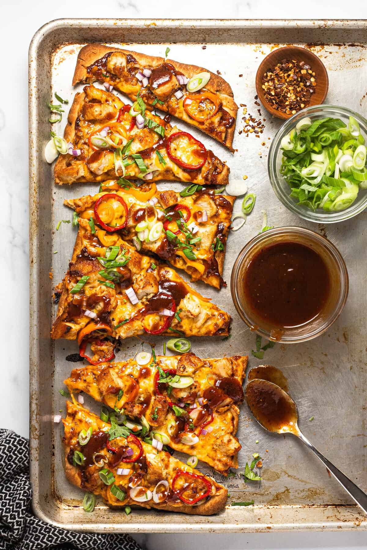 Baking sheet with a BBQ chicken flatbread garnished with sliced green onion