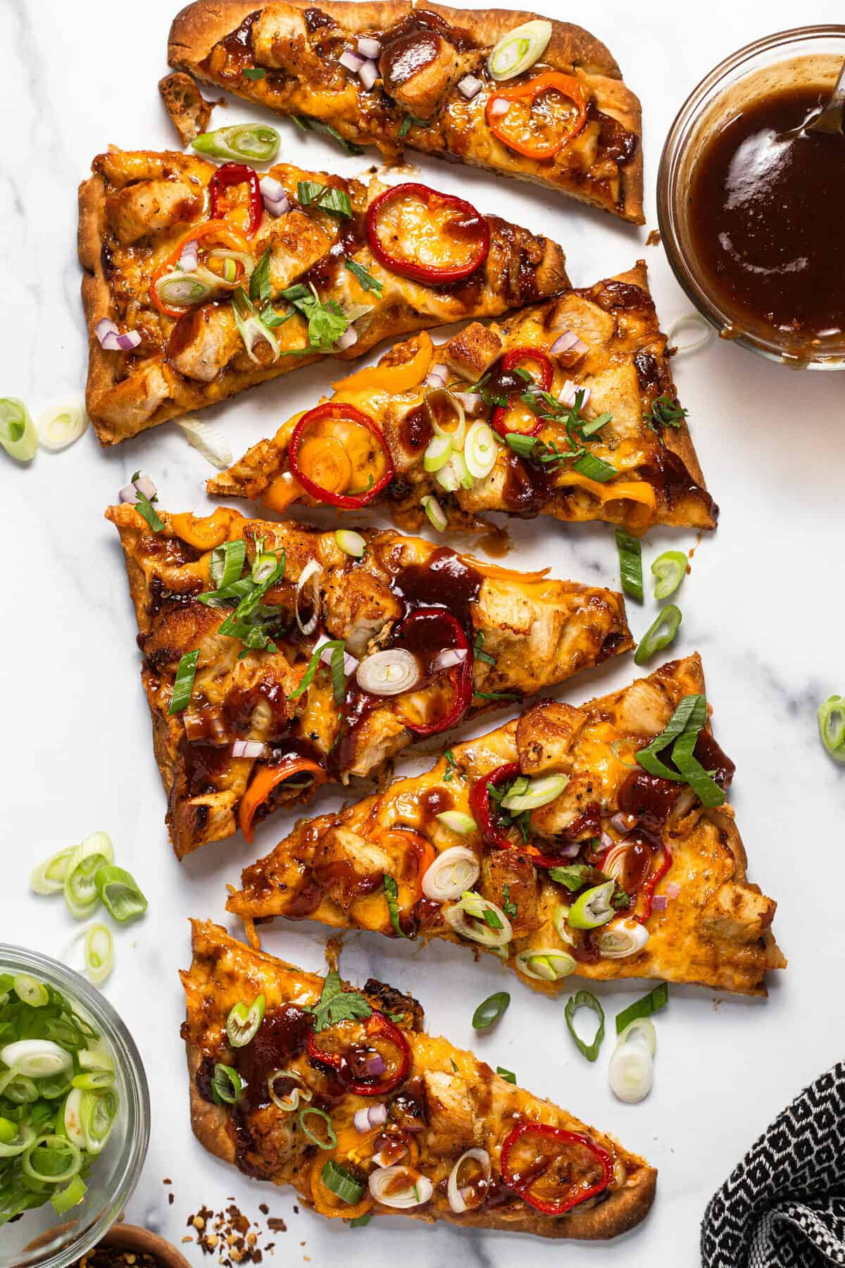 BBQ chicken flatbread garnished with sliced green onion on a white marble countertop