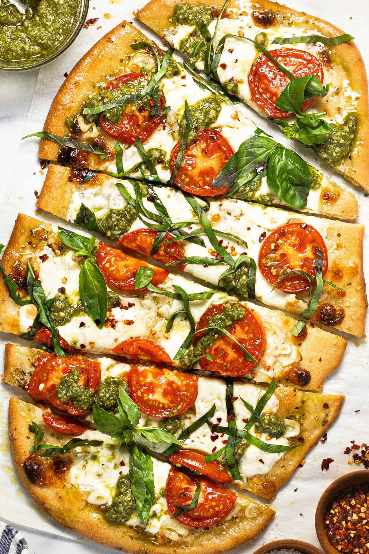Close up shot of sliced margherita flatbread pizza garnished with basil